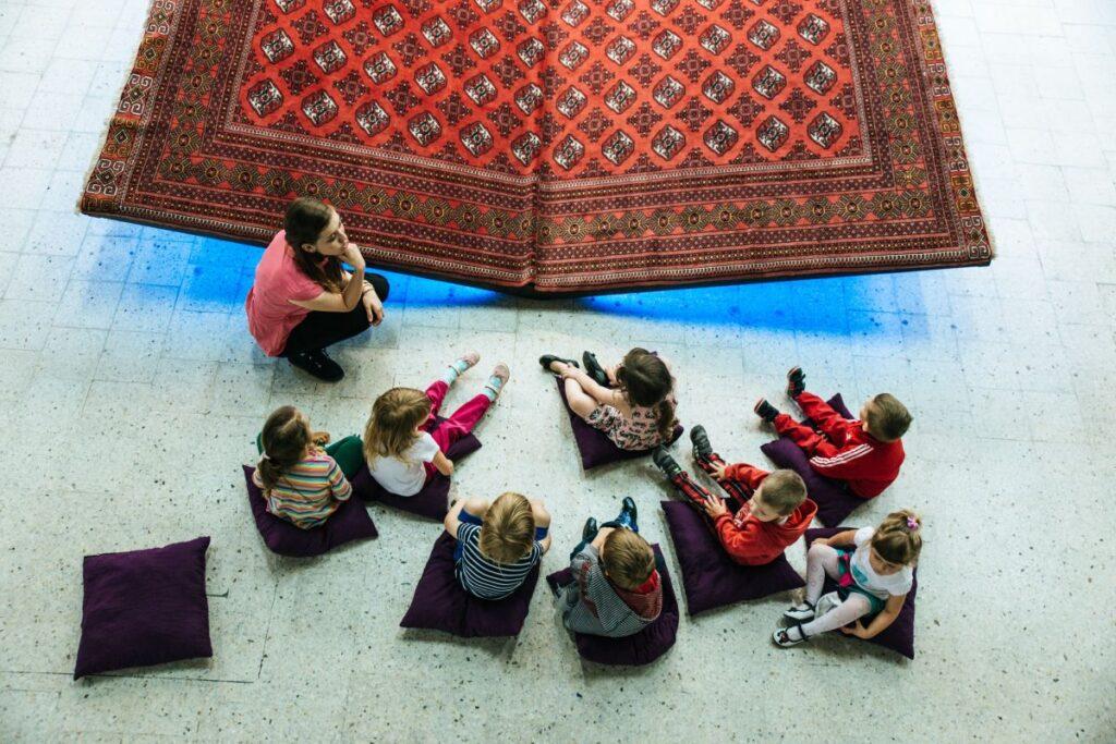 8 copii preșcolari stau pe jos pe pernițe și învață engleza de la profesoara lor in fata unui covor urias sub forma de carte