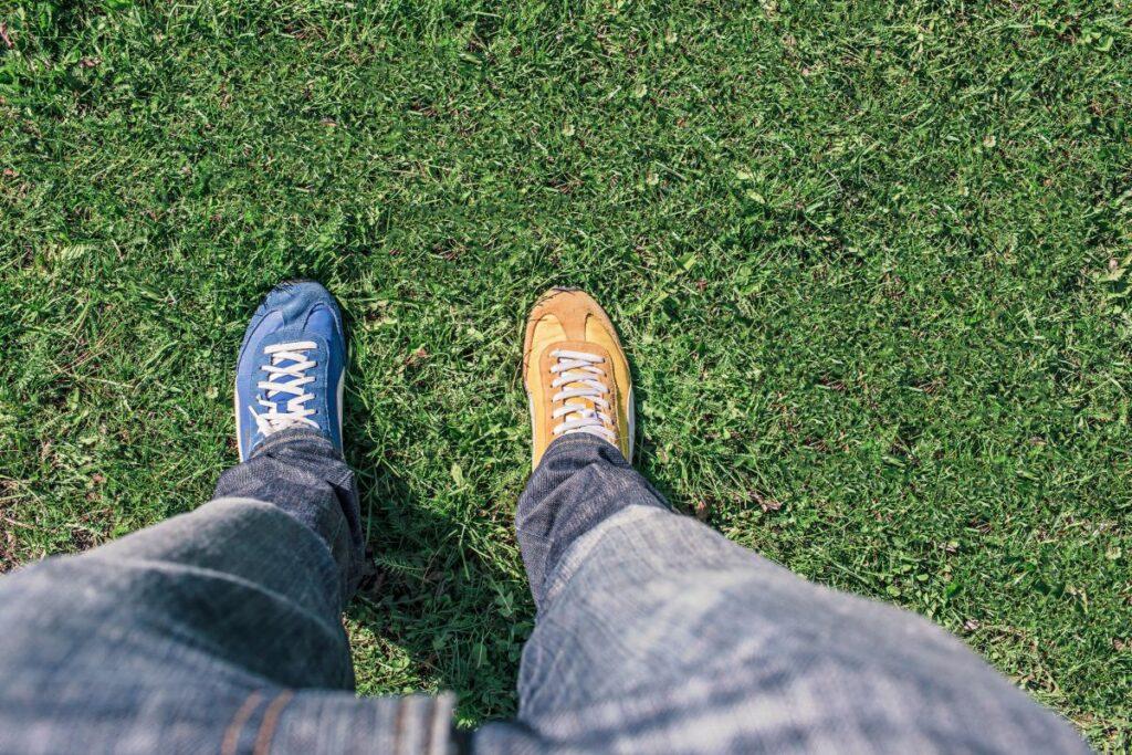 picioare fotografiate de sus imbracate in blugi si cu doi pantofi de culori diferite portocaliu si albastru stand pe gazon