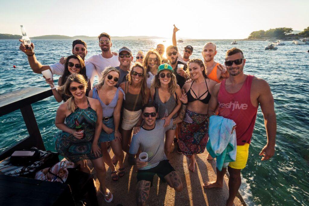 Grup de tineri din diferite tari purtand haine de vara si ochelari de soare pe un ponton la mare care se distreaza impreuna si converseaza in engleza la o petrecere