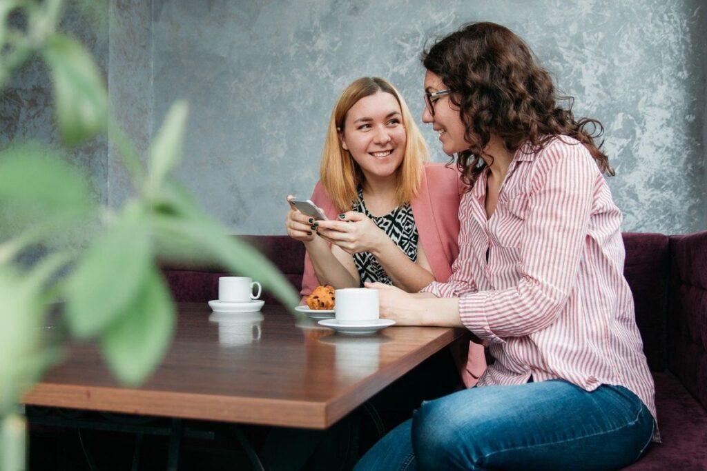 Doua femei de nationalitati diferite stau intr-o cafenea la o masa joasa de lemn, beau cafea si converseaza pentru a invata o limba straina discutand despre o poza din telefonul uneia dintre ele