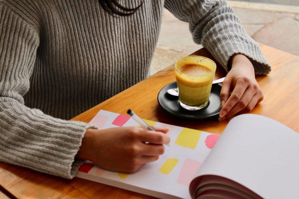 Femeie asezata la birou cu o ceasca de cafea in fata care se pregateste scriind pe o agenda colorata cuvinte si expresii utile pentru o conversatie in limba engleza