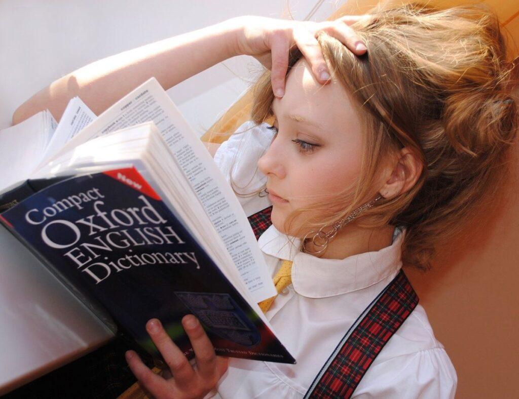 elevă blonda imbracata in uniforma cu camasa alba care priveste intr-un dictionar de limba engleza deschis unde se afla multe cuvinte noi