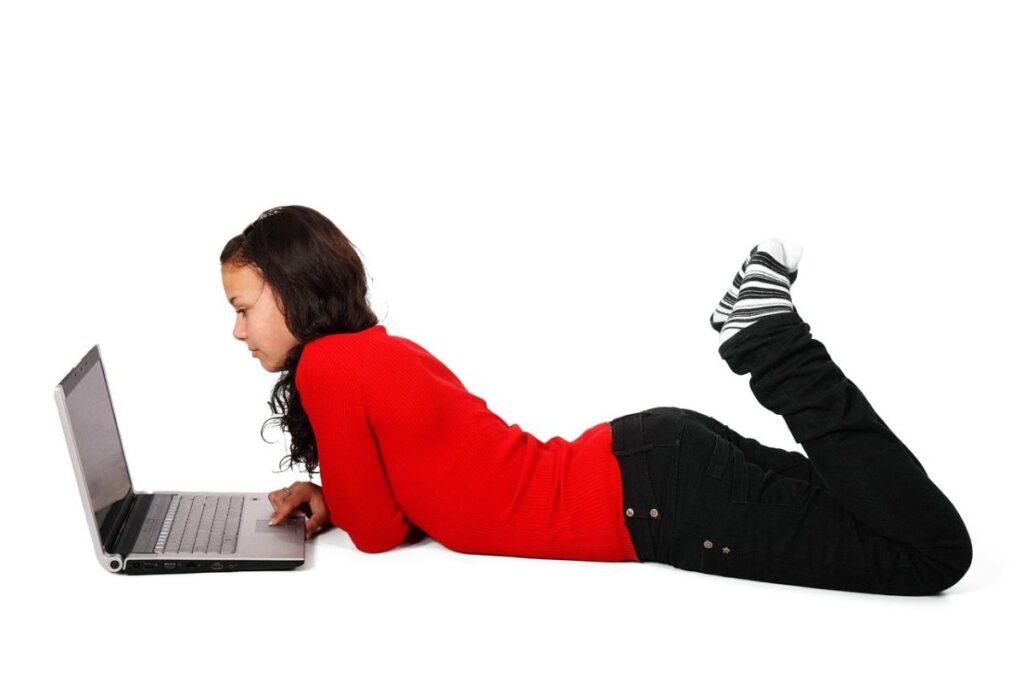 femeie imbracata in bluza rosie, pantaloni negri si soseste cu dungi sta comod intinsa pe burta pe podea si priveste la laptop unde asculta un curs online de engleza pentru incepatori
