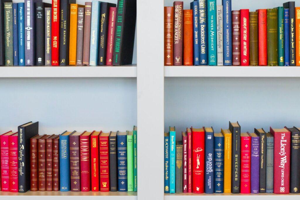 4 rafturi de carti multicolore in engleza intr-o biblioteca alba