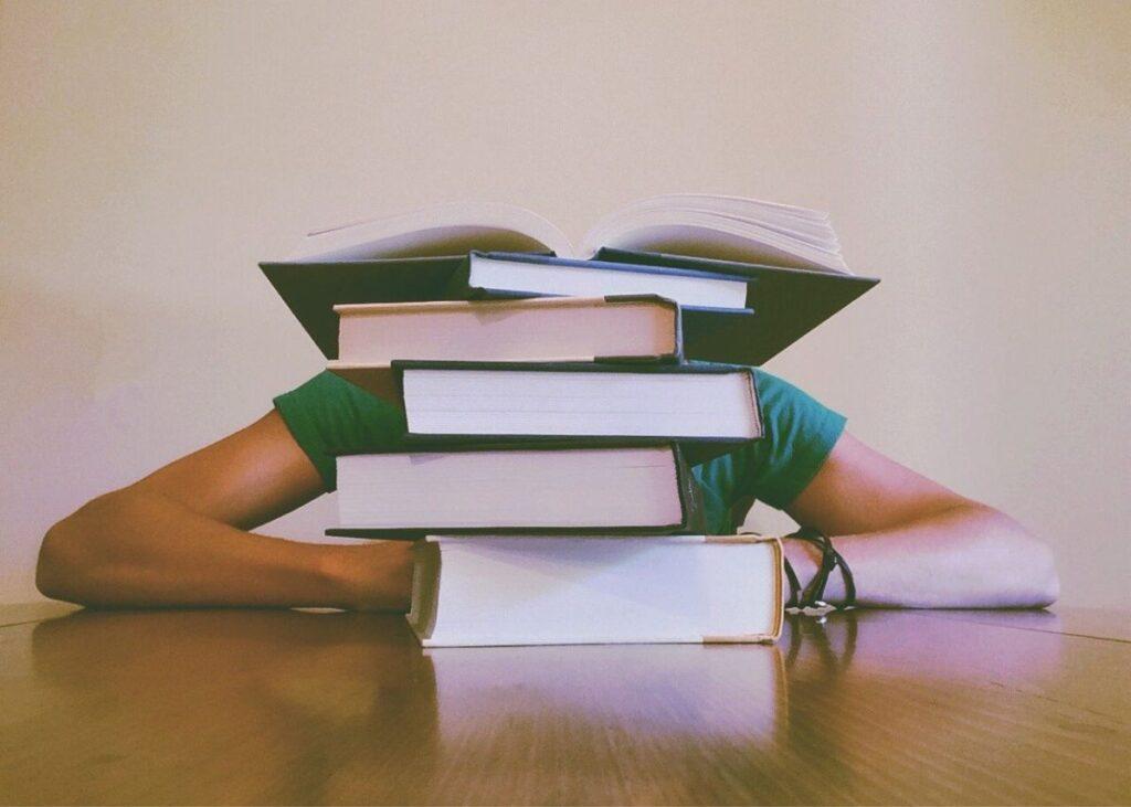 copil imbracat in tricou verde asezat la birou de lemn natur avand in fata un teanc de carti pentru pregatire examen Cambridge astfel incat nu i se vede capul si nici corpul