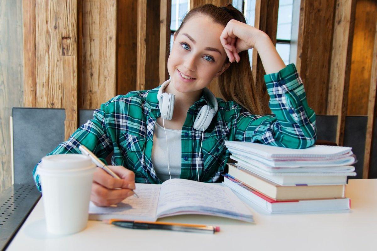 adolescenta cu parul lung prins in coada, imbracata in tricou alb si camasa in carouri verde cu albastru stă la birou alb pe care e un teanc de carti si un caiet deschis pe care ea scrie exercitii de pregatire pentru examenul Cambridge