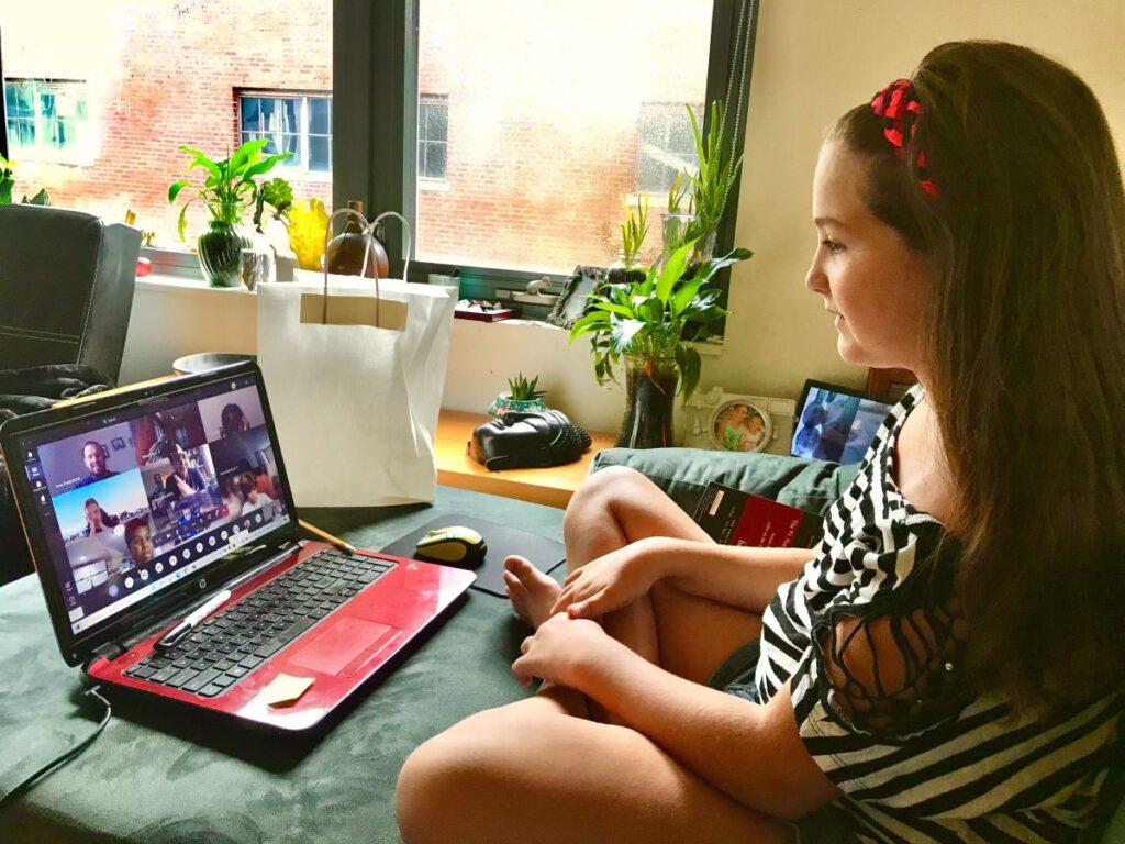 adolescenta cu parul lung brunet sta comod acasa imbracata casual si participa la un curs online de engleza in fata laptopului ei