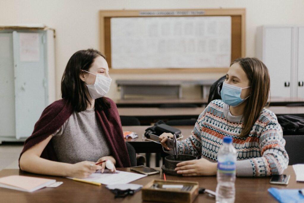 Doua adulte purtand masca stau in banca impreuna si converseaza in timpul unei ore