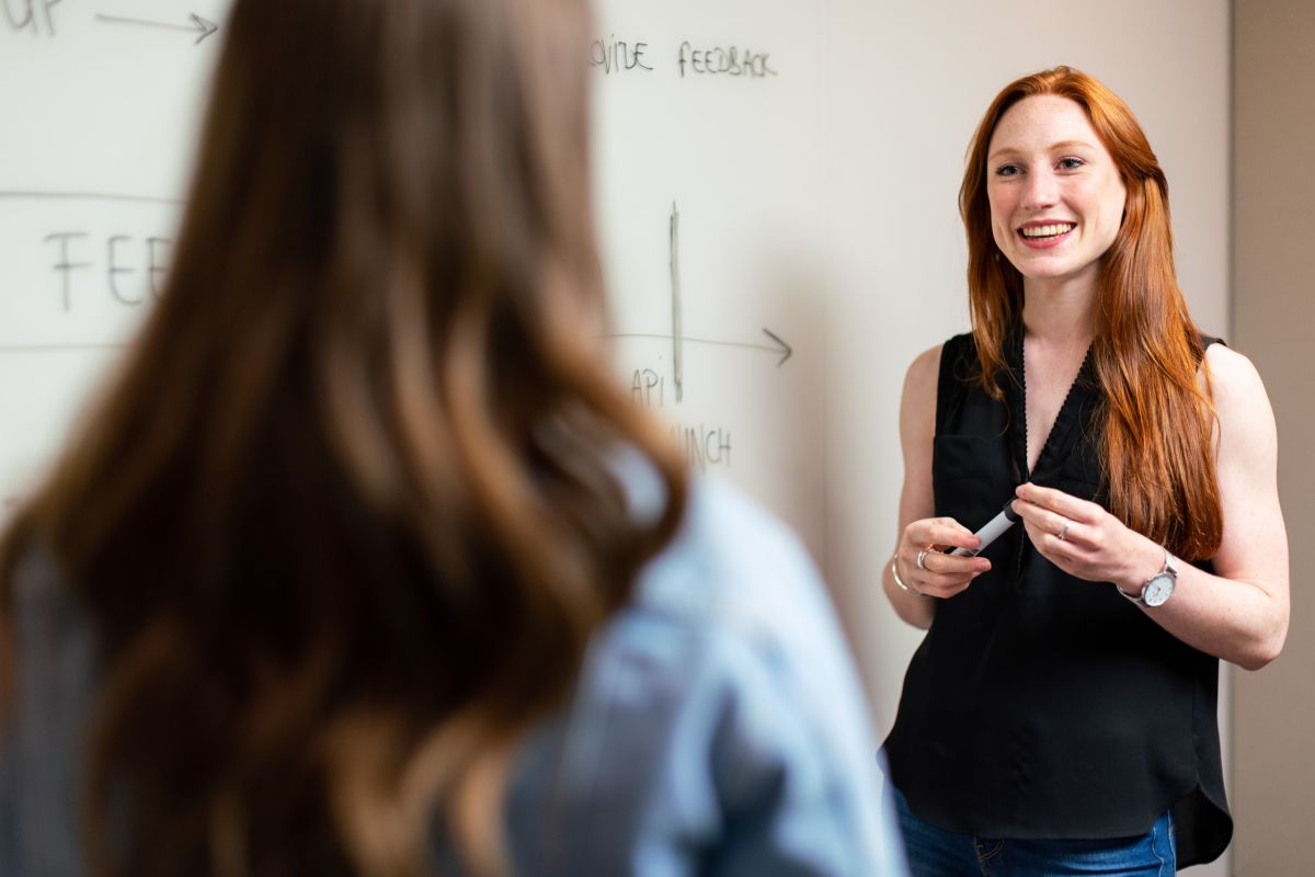 profesoara de engleza cu parul lung roscat imbracata in top negru sta langa tabla zambind cu un marker in mana pentru a ii explica unei cursante ceva