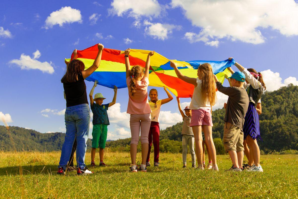 grup de 8 copii imbracati lejer de vara pe un camp langa o padure care tin deasupra capului o panza mare multicolora si invata prin diverse metode despre natura
