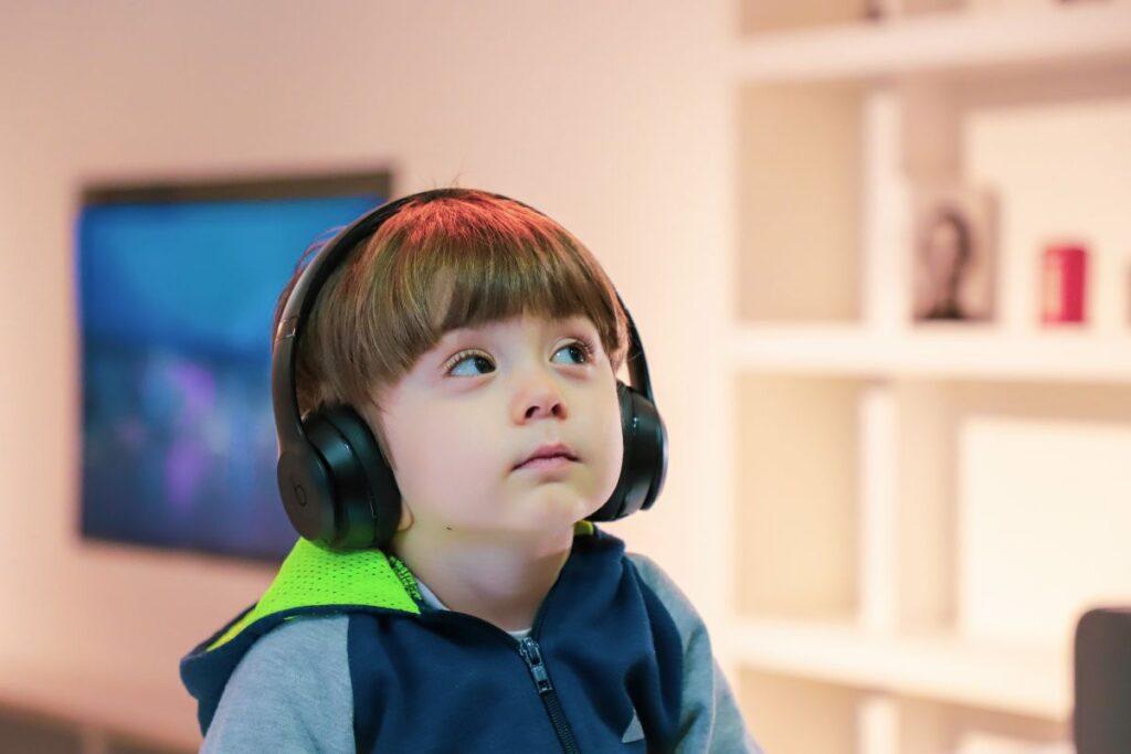baietel imbracat in hanorac albastru cu verde asculta la niste casti mari o poveste audio si invata limbi straine in sufrageria sa