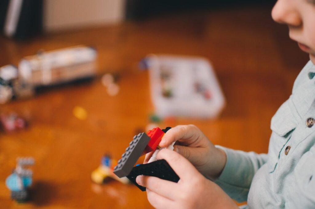 profil si manute de copil in prim plan care construieste ceva cu piese tip Lego, avand podeaua cu jucarii in fundal, blurata
