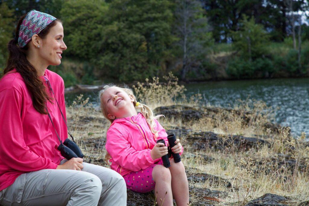 mama si fetita ei imbracate in jachete roz aflate in natura pe malul unui rau privesc cu binoclul natura si discuta