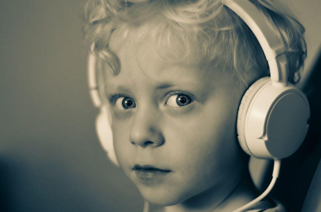 Chip de copil blond cret cu casti mari albe care asculta o poveste audio si priveste spre camera in prim plan