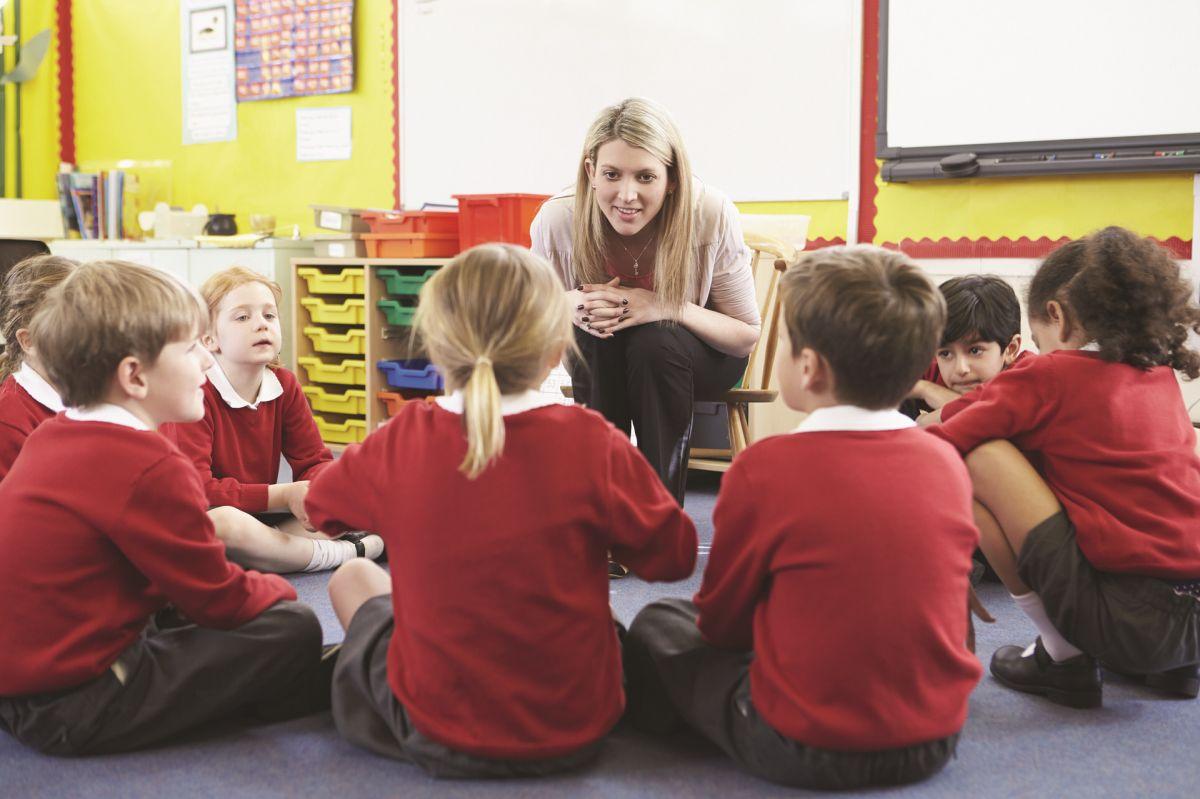 profesoara in sala de clasa care a asezat o grupa de copii imbracati in uniforma rosie cu gri in semicerc pe podea si le spune povesti pentru a ii invata prin metoda auditiva