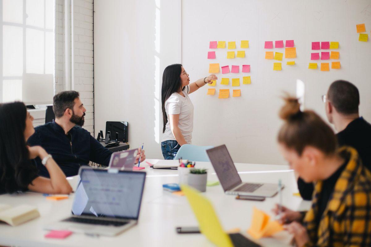 sala de sedinte la o multinationala unde angajatii stau in jurul unui birou mare cu laptopurile deschise si asculta o colega vorbind in engleza si aratandu-le diverse idei ale sale