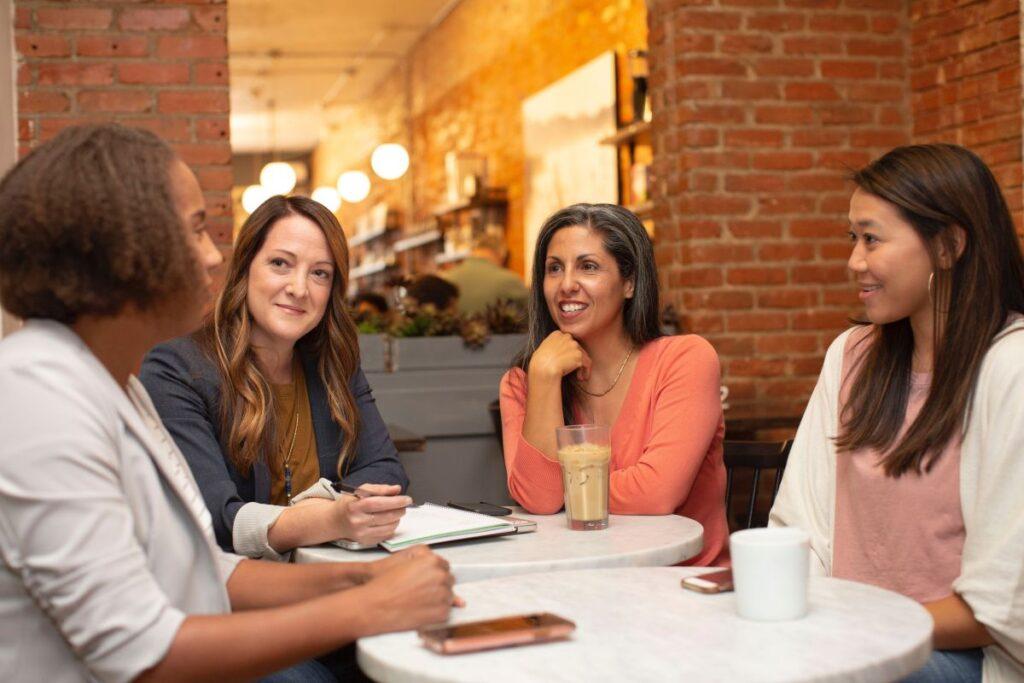 patru femei in jurul unei mese la o cafenea converseaza in engleza despre locul de munca si socializeaza