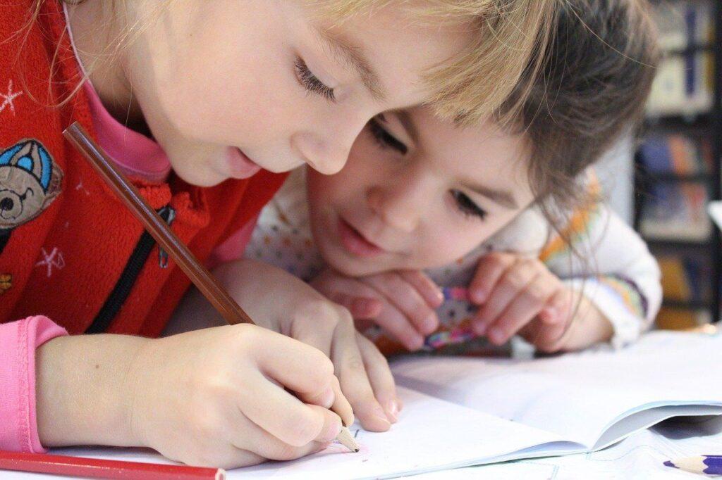 fetite de varsta scolara aplecate deasupra unui birou scriu pe un caiet propozitii in engleza