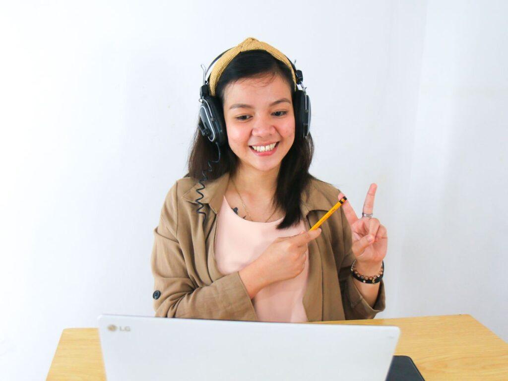 Tanara asezata in fata laptopului cu casti mari pe urechi participa la un curs de engleza conversational online si arata cu degetele semnul victorie