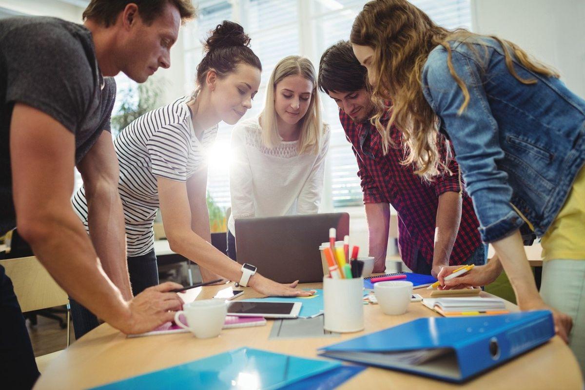 grup de lucru de adulti care stau in picioare aplecati asupra unui birou si studiaza limba engleza