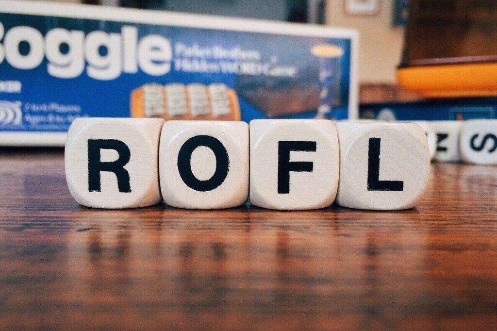 acronim ROFL scris din litere negre imprimate pe cuburi albe puse pe o masa de lemn