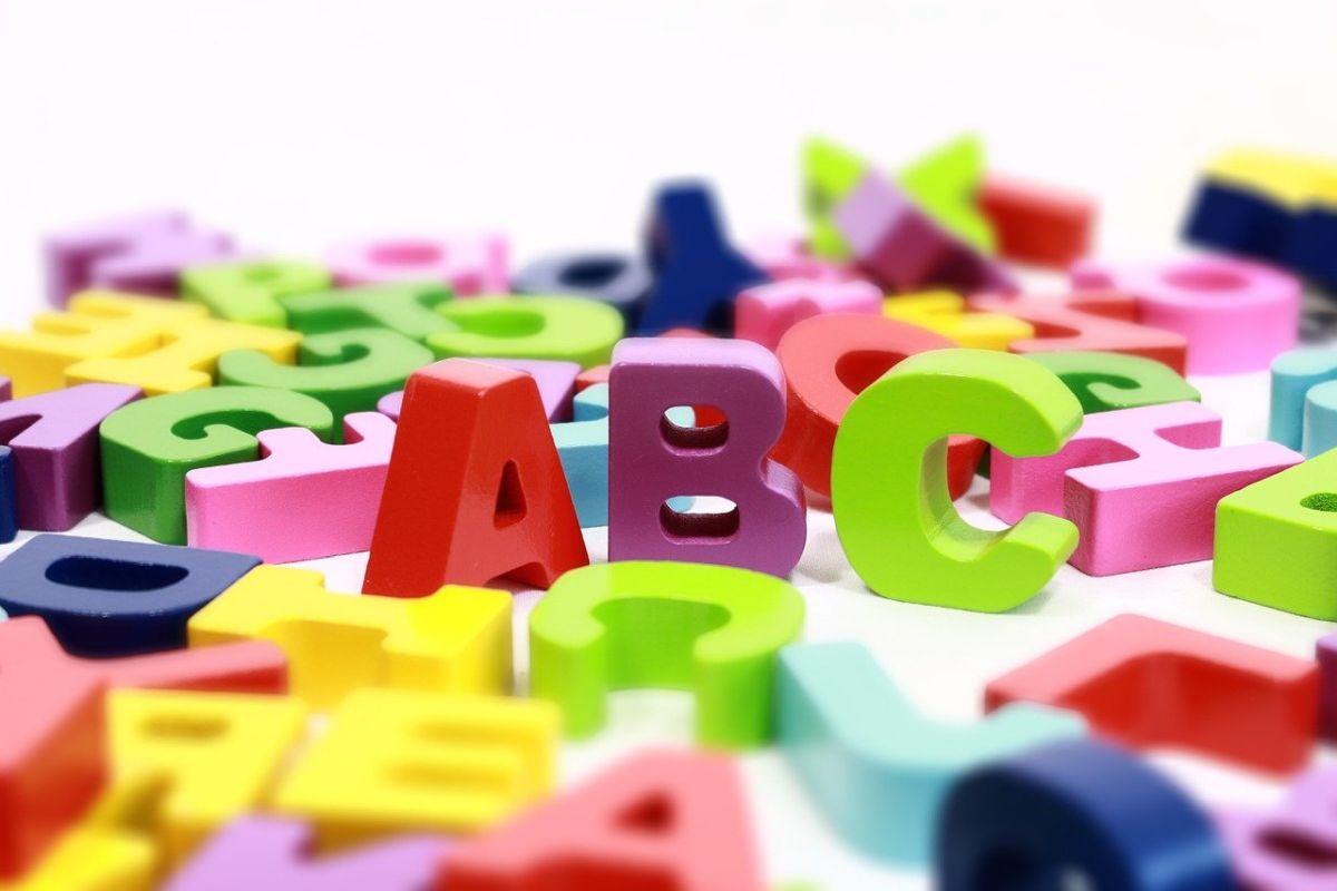litere de lemn de culori diferite vibrante din alfabetul limbii engleze pe fundal alb