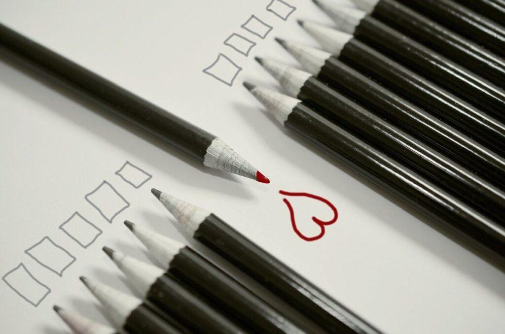 set de creioane negre in varful carora e desenat cate un patrat avand in mijloc un creion rosu dispus invers, in fata caruia e desenata o inimioara