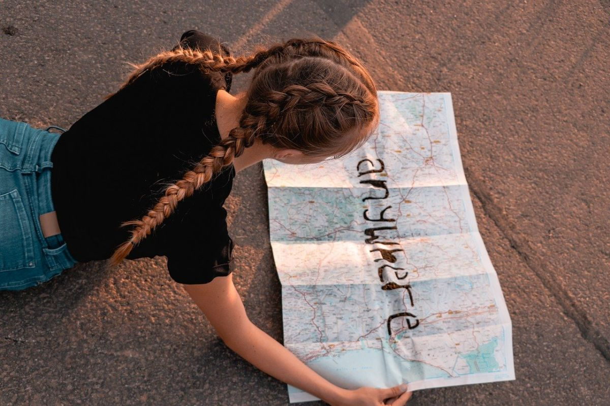 tanara cu 2 cozi lungi impletite in tricou negru si jeansi albastri sta pe burta pe asfalt privind o harta a lumii peste care e scris cuvantul anywhere in engleza