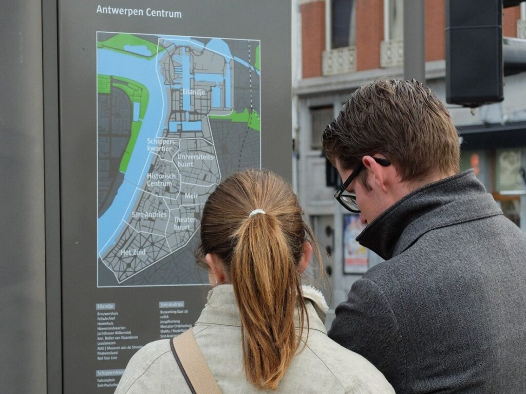 doi turisti, barbat si femeie, care privesc o harta pe un panou intr-un oras strain si se pregatesc sa ceara indicatii in limba engleza