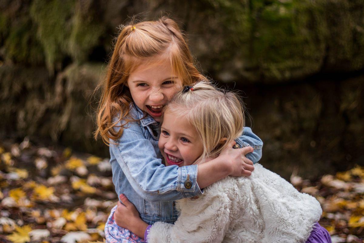 Doua fetite, roscata si blonda, se joaca si se imbratiseaza intr-un parc