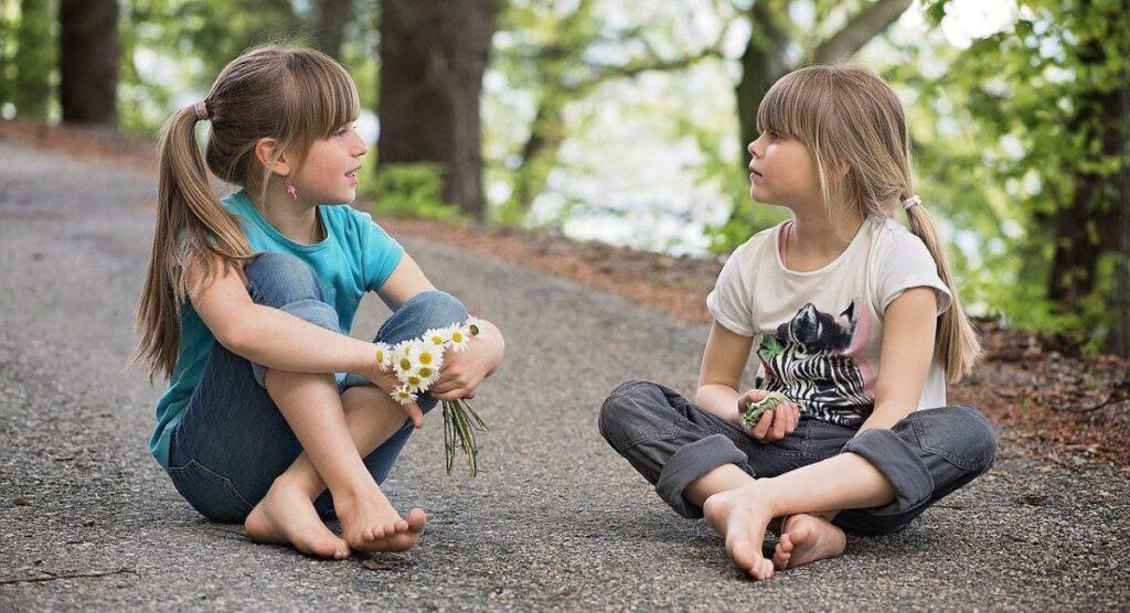 doua fetite stau pe jos desculte pe un drum in padure si vorbesc legand o prietenie
