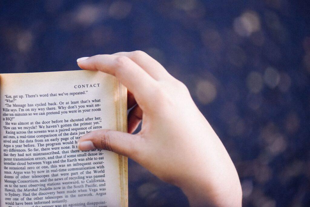 Mana de femeie care tine o carte deschisa in limba engleza pe fundal albastru blurat
