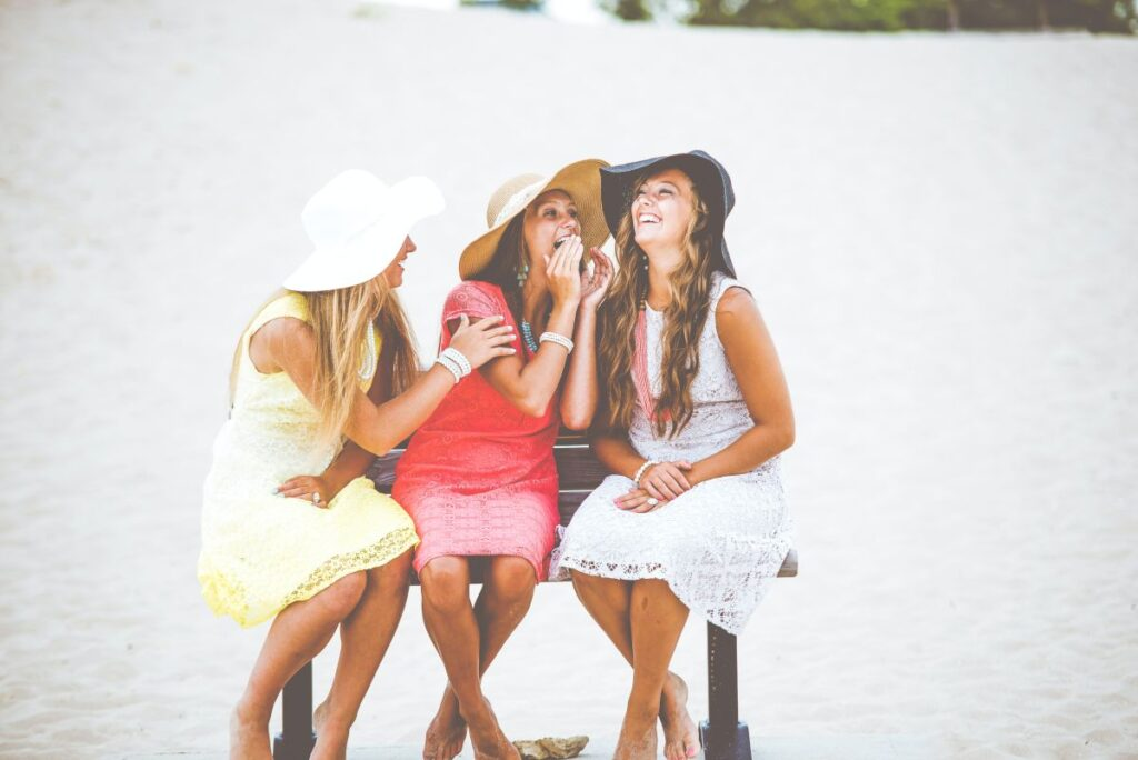 trei prietene cu rochii si palarii stau pe o banca pe malul mării cu spatele la apa si joaca un joc amuzant de ghicit in limba engleza