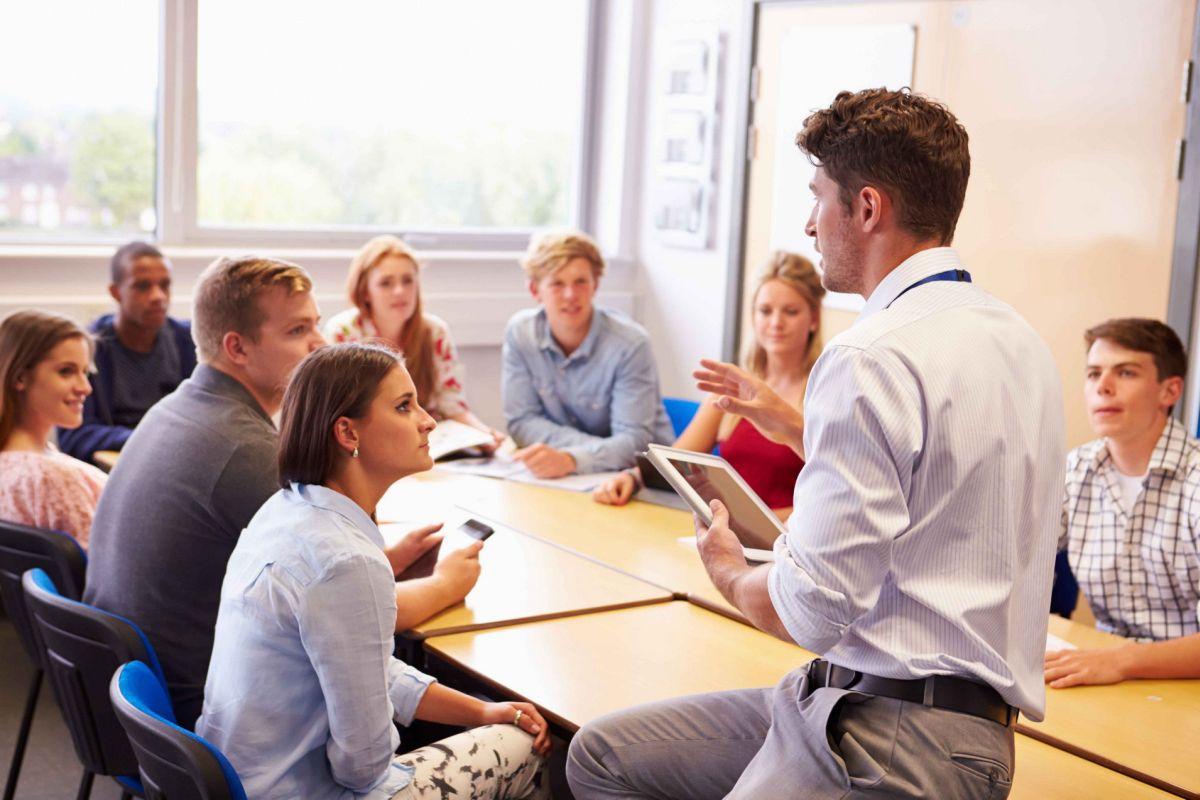 clasa de adulti asezati in jurul unei mese la un curs de limba engleza cu profesorul care le explica ceva