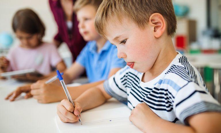Baietel care scrie ceva cu pixul pe caiet la cursul de engleza concentrat, asezat in banca in sala de clasa