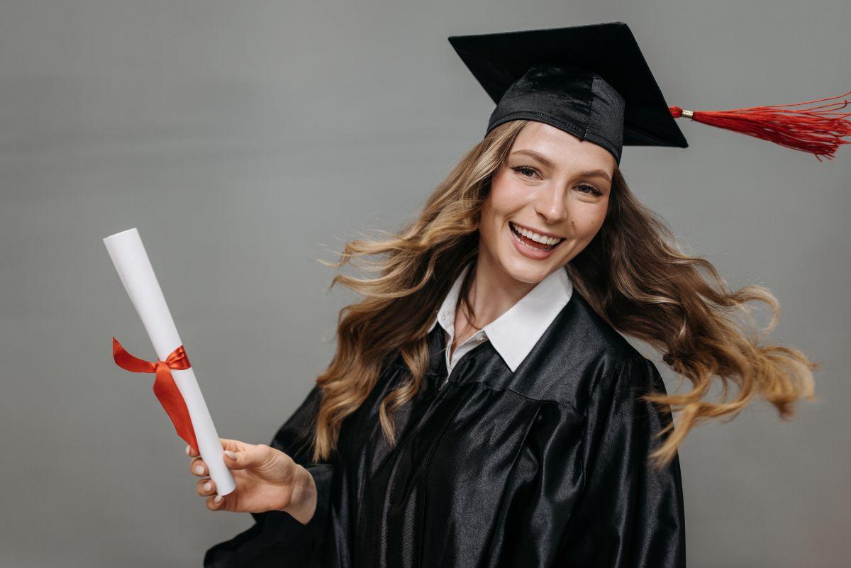 absolventa imbracata in toga fericita, tine o diploma rulata in mana