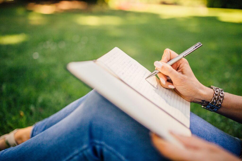 prim plan pe un caiet tinut pe genunchi de o fata imbracata in blugi care sta pe iarba si scrie