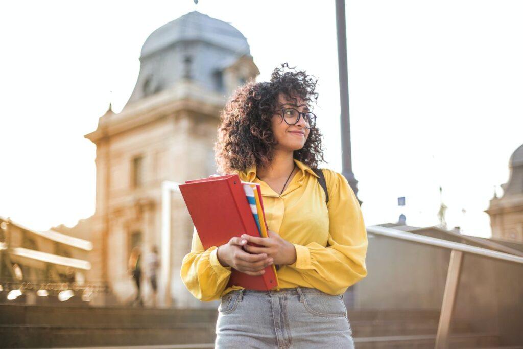 Tanara creata cu ochelari imbracata in galben sta zambind in fata unei universitati straine de prestigiu avand un dosar rosu in mana