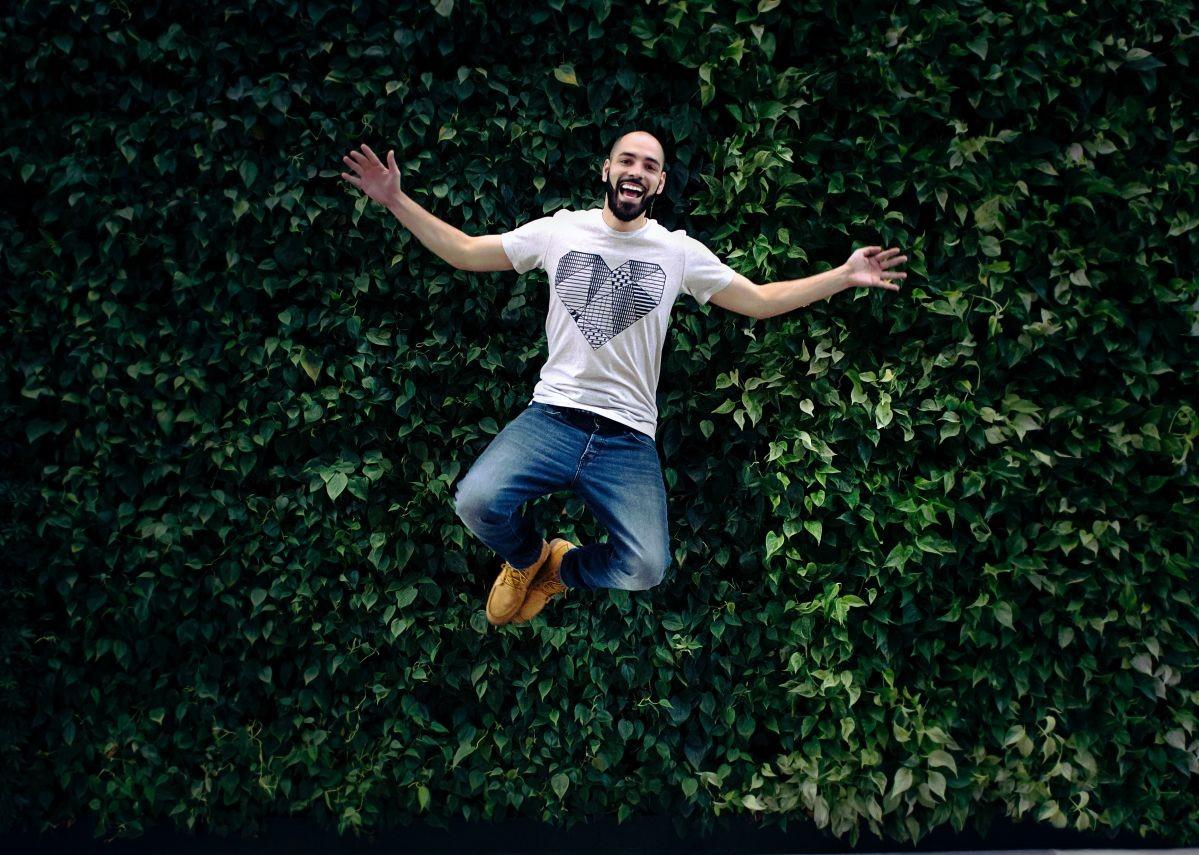 barbat imbracat casual in blugi si tricou care sare in aer in fata unui gard viu tip perete