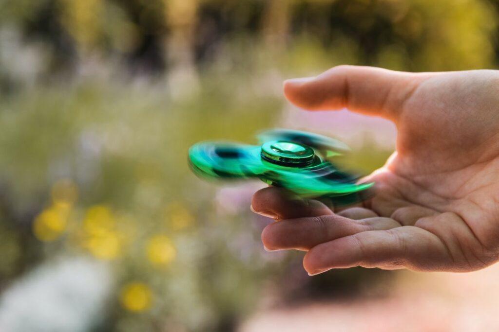 mana in prim plan care tine pe aratator un titirez metalic verde ce se invarteste, avand ca fundal un peisaj blurat
