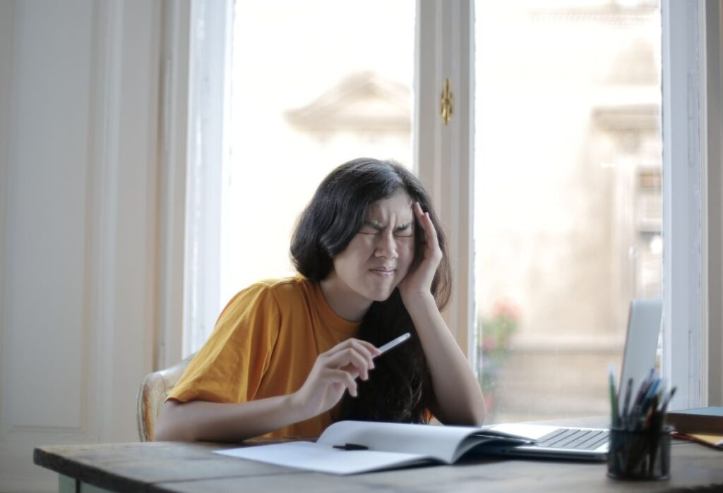 tanara asezata la birou care incearca sa retina informatia dintr-o carte dar ii e foarte greu sa se concentreze si o doare capul