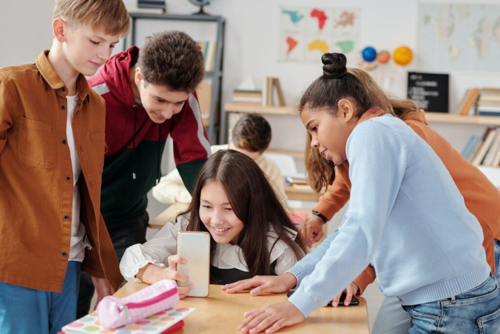 copii adolescenti in sala de clasa la cursul de engleza citesc ceva pe un telefon si se amuza