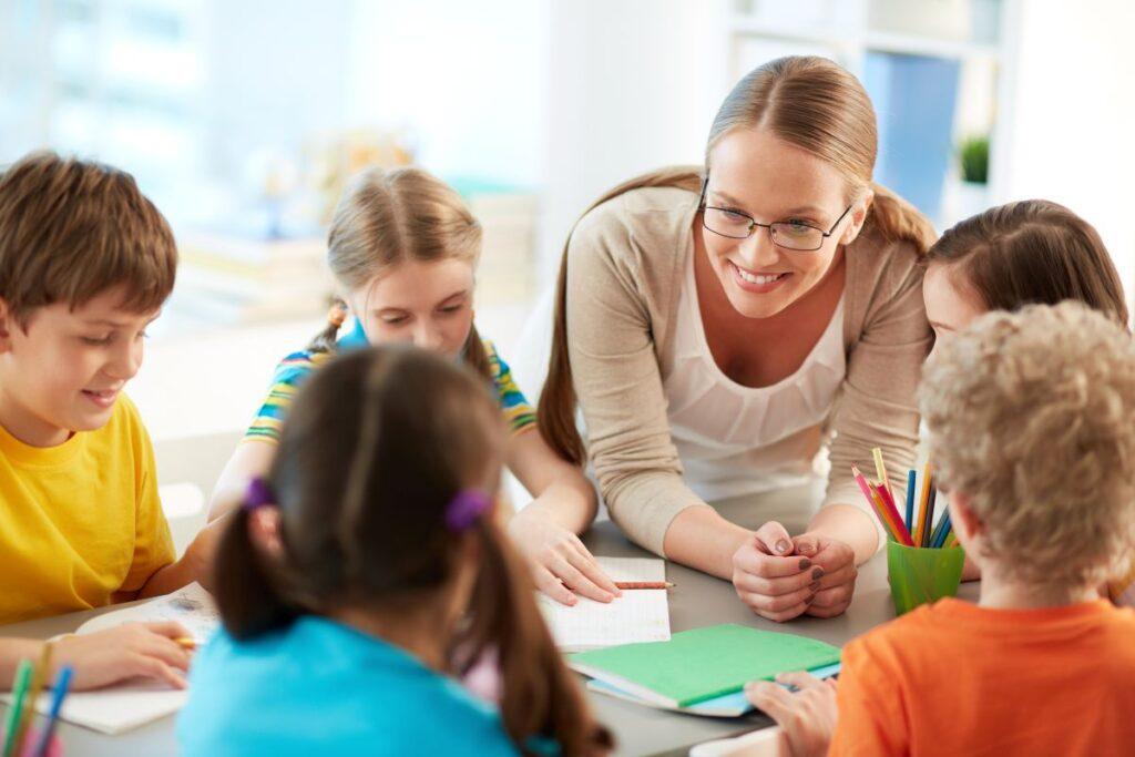 profesoara blonda foarte tanara care le zambeste copiilor in clasa