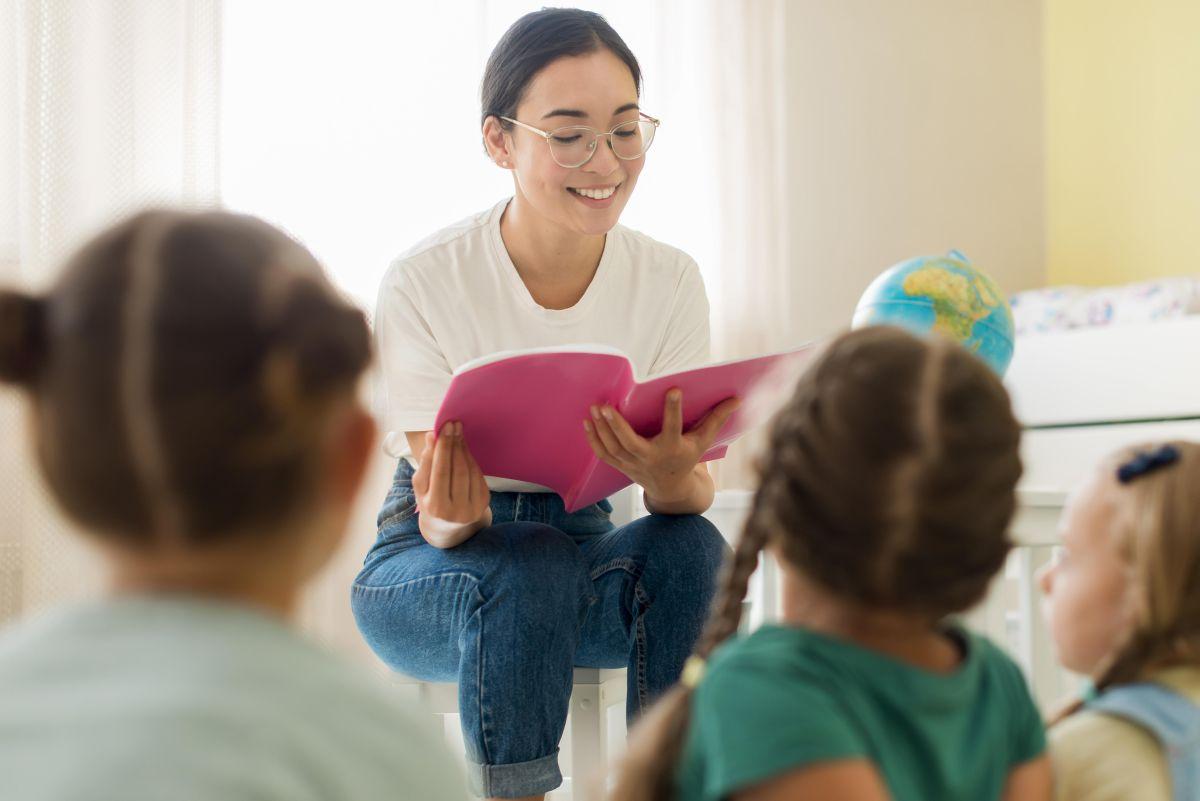 profesoara tanara cu chipul bland le citeste copiilor asezati in fata ei, cu spatele la obiectiv, o poveste