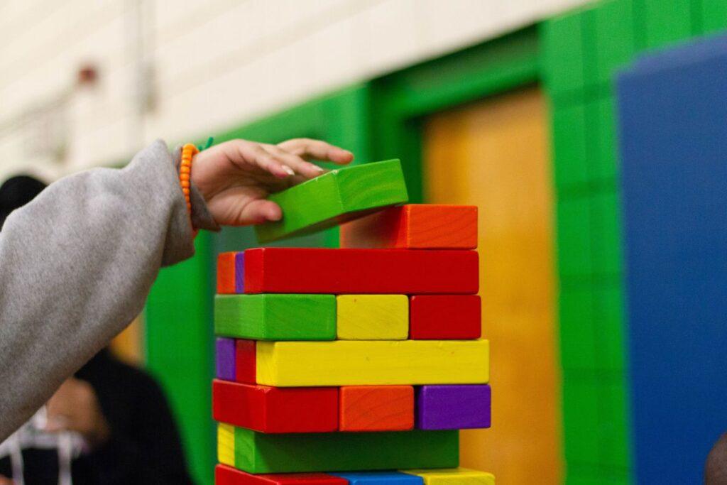 mana de copil care construieste un turn impresionant din cuburi de lemn