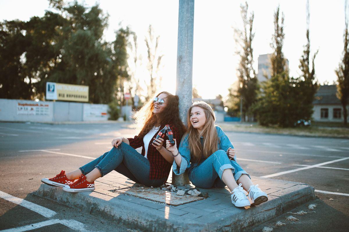 doua tinere imbracate sport stau jos langa un stalp de electricitate si zambesc fericite ca au invatat ceva nou dand noroc cu sticle de Cola