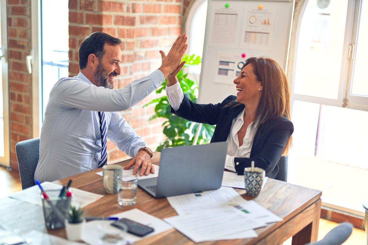 doi parteneri de afaceri barbat si femeie intr-un birou bat palma si incheie o intelegere