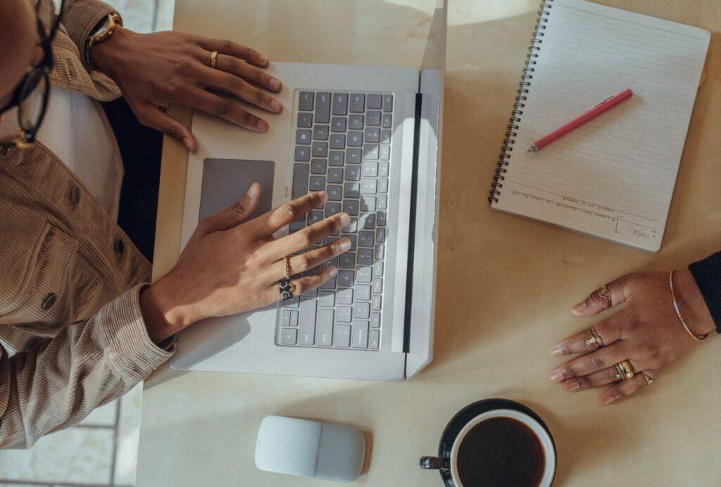 privire de sus asupra corpului si mainilor unei candidate care sustine examenul pe calculator, avand alaturi un mouse si o ceasca de cafea