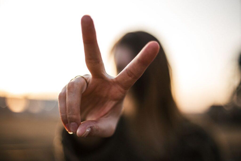 tanara in fundal care arata in prim plan semnul victoriei cu degetele
