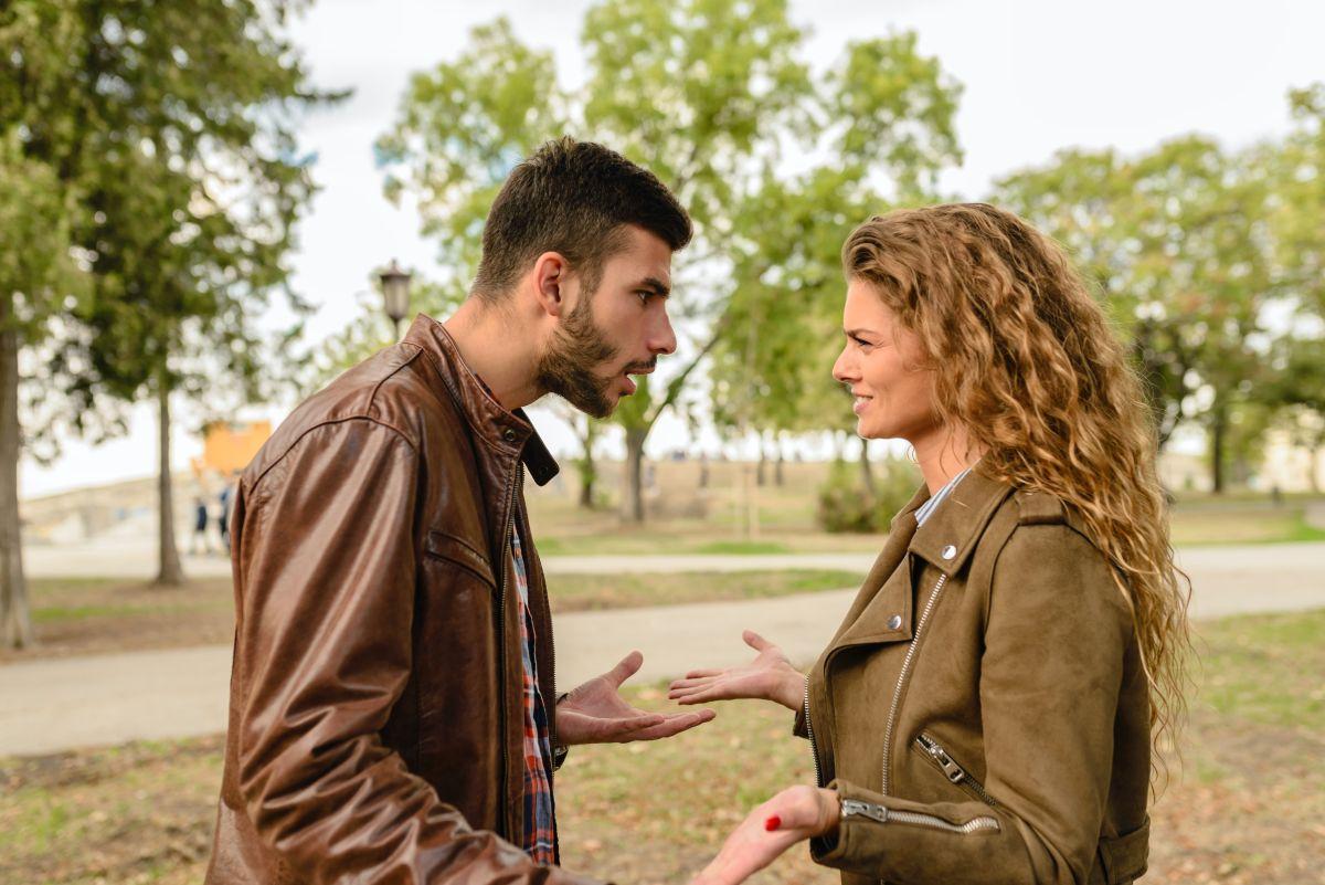 doi tineri in aer liber barbat si femeie care incearca sa se inteleaga prin gesturi
